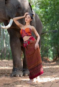 Porträt der frau im traditionellen kostüm, das mit elefanten steht