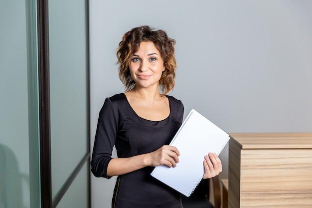 Porträt der frau im weißen büro mit dokumenten isoliert.
