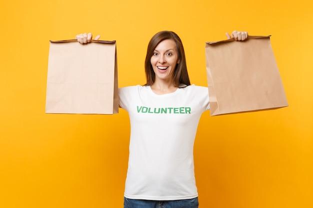 Porträt der frau im weißen t-shirt geschrieben inschrift grüner titel freiwilliger halten leere handwerkspapiertüte zum mitnehmen isoliert auf gelbem hintergrund. freiwillige kostenlose hilfe hilft konzept der nächstenliebe