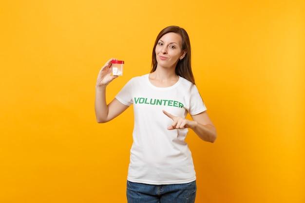 Porträt der frau im weißen t-shirt geschriebener aufschrift grüner titel freiwilliger, der flasche mit pillendroge lokalisiert auf gelbem hintergrund hält. freiwillige kostenlose hilfe, gesundheitskonzept der wohltätigkeitsgnade.