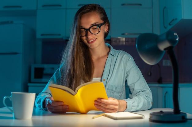 Porträt der frau in den gläsern, die abends zu hause ein buch lesen