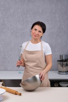 Porträt der frau in der küche in der küchenschürze. vertikaler rahmen.