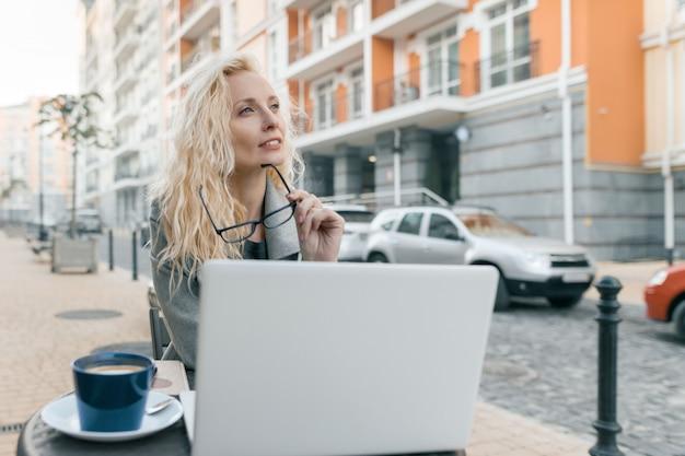 Porträt der frau in der warmen kleidung, die in einem straßencafé mit laptop sitzt