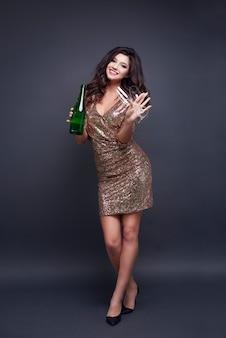 Porträt der frau in voller länge mit champagnerflöte und flasche
