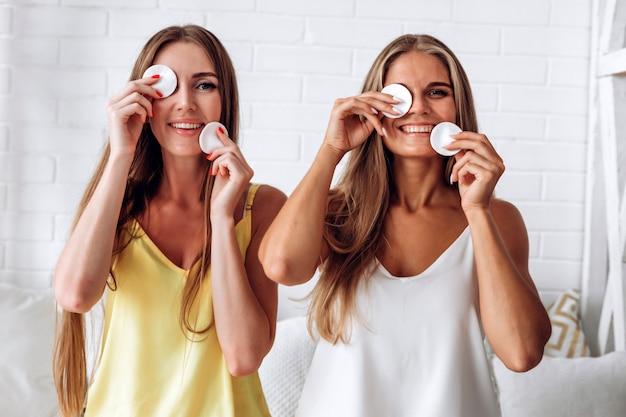 Porträt der frau lächelnd und baumwollauflage gegen weißen hintergrund verwendend