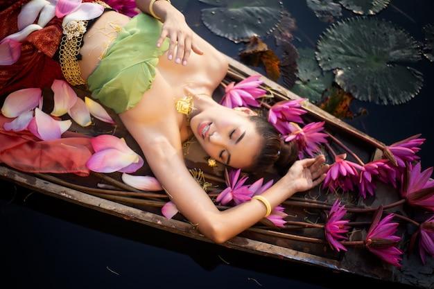 Porträt der frau liegend auf boot durch rosa lotus in lake
