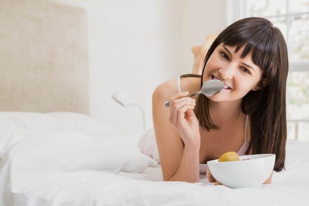 Porträt der frau liegend und auf bett im schlafzimmer frühstückend
