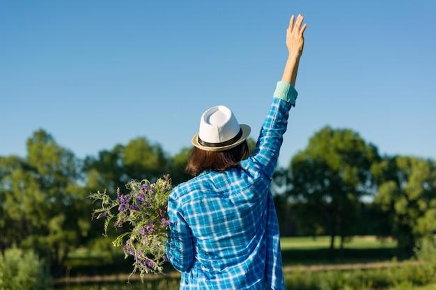 Porträt der frau mit blumenstrauß von wildblumen