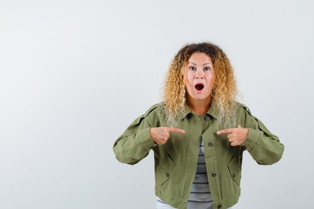 Porträt der frau mit dem lockigen blonden haar, das auf sie in der grünen jacke zeigt und verwirrte vorderansicht schaut