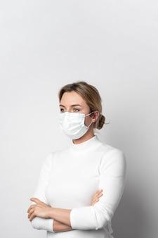 Porträt der frau mit der aufstellenden chirurgischen maske