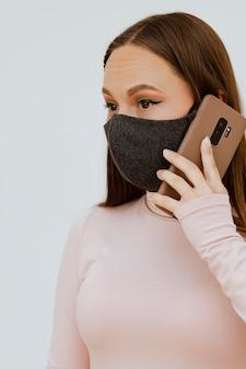 Porträt der frau mit der medizinischen maske, die auf smartphone spricht