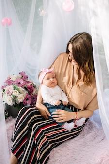 Porträt der frau mit einem niedlichen baby. schöne frau mit einem kleinen baby