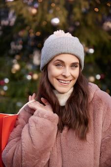 Porträt der frau mit einkaufstasche auf weihnachtsmarkt