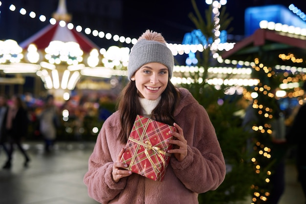 Porträt der frau mit geschenken auf dem weihnachtsmarkt