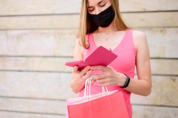 Porträt der frau mit gesichtsmaske, die einkaufstasche hält