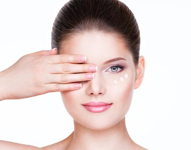 Porträt der frau mit gesundem gesicht, das kosmetische creme unter den augen anwendet.