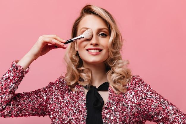 Porträt der frau mit gewelltem haar, das ihr auge mit make-up-pinsel bedeckt