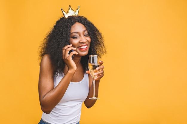 Porträt der frau mit glas champagner und goldener krone, die am telefon sprechen
