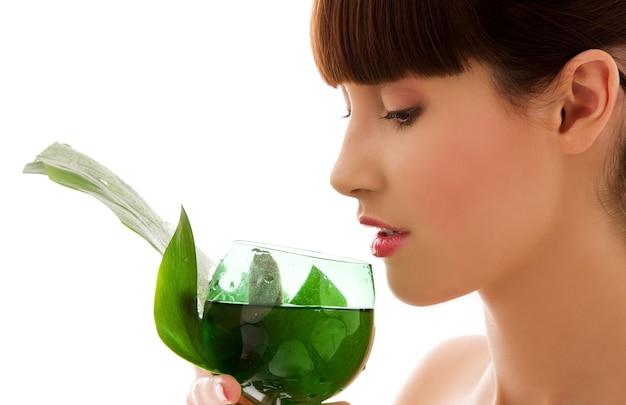 Porträt der frau mit grünem blatt und glas wasser