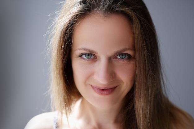 Porträt der frau mit hellbraunem haar und blauen augen.