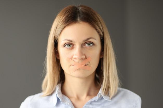 Porträt der frau mit klebeband geklebten mund. psychologie der weiblichen stille. konzept