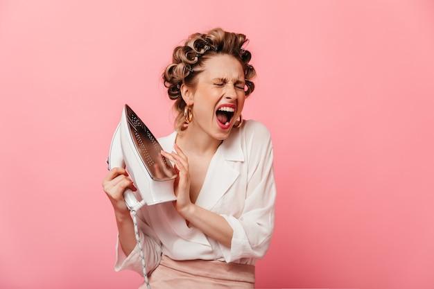 Porträt der frau mit lockenwicklern, die eisen berühren und vor schmerz auf rosa wand schreien