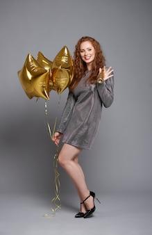 Porträt der frau mit luftballons und champagner bei studioaufnahme