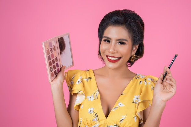 Porträt der frau mit make-upbürste und kosmetik