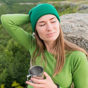 Porträt der frau mit mütze, die thermoskanne hält