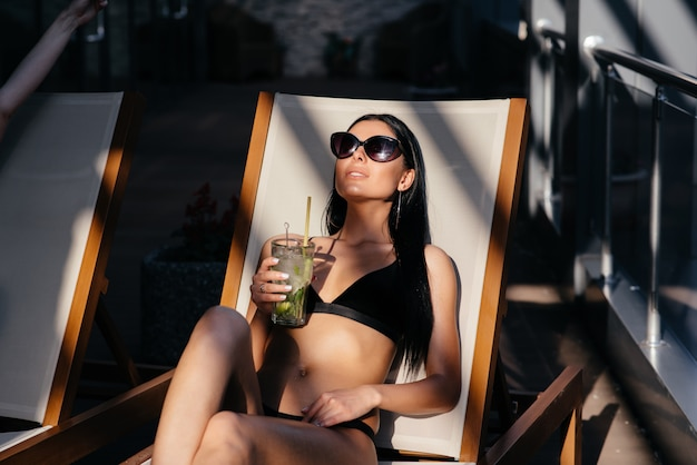 Porträt der frau mit perfekt gebräuntem sitzkörper, der die modische sonnenbrille trägt, die cocktail trinkt