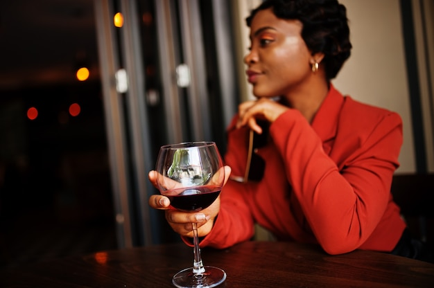Porträt der frau mit retro-frisur trägt orange jacke im restaurant mit glas wein