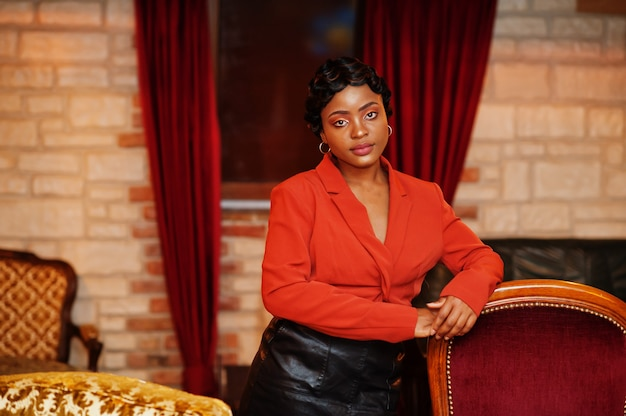 Porträt der frau mit retro-frisur trägt orange jacke im restaurant