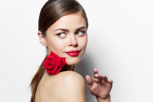 Porträt der frau mit rose blickt beiseite luxuslippenhintergrund der roten lippen