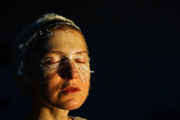 Porträt der frau mit transparentem film auf ihrem gesicht