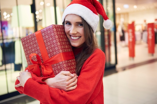 Porträt der frau mit weihnachtsgeschenk im laden