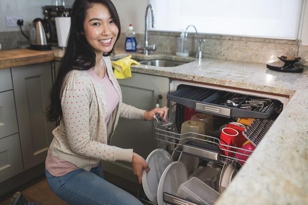 Porträt der frau platten in der spülmaschine vereinbarend