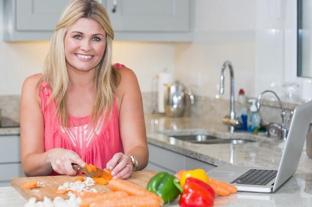 Porträt der frau rezept vom internet auf laptop in der küche machend