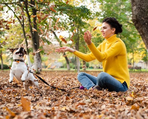 Porträt der frau spielend mit ihrem hund im park