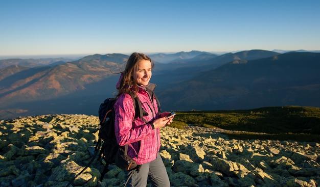 Porträt der frau stehend auf felsiger spitze des berges
