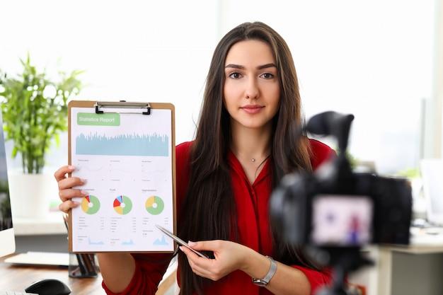 Porträt der frau vlogger, die papierordner mit finanzbericht hält.