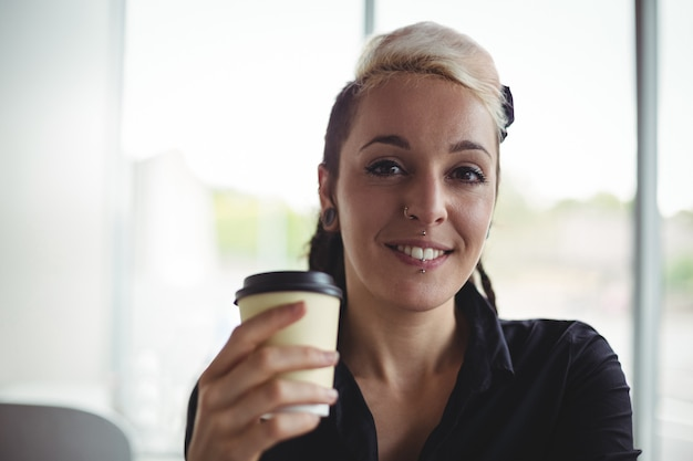 Porträt der frau wegwerfkaffeetasse halten