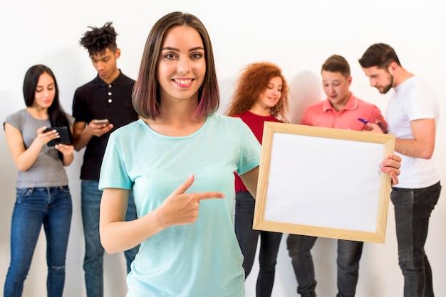 Porträt der frau zeigend in richtung zum leeren weißen rahmen während ihre freunde beschäftigt im mobiltelefon