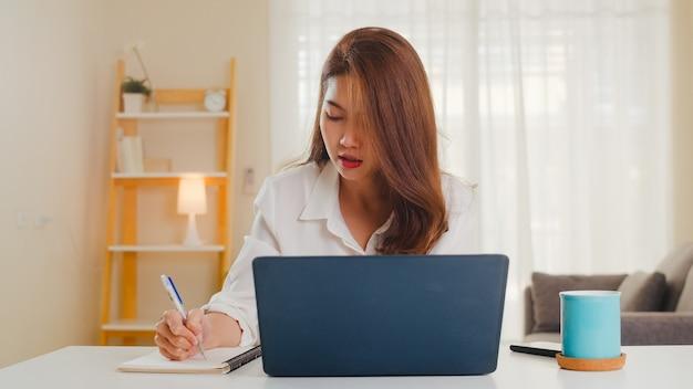 Porträt der freiberuflichen freizeitkleidung der asiatischen frauen unter verwendung des laptops, der im wohnzimmer zu hause arbeitet. arbeiten von zu hause aus, fernarbeit, selbstisolierung, soziale distanzierung, quarantäne zur vorbeugung von coronaviren.