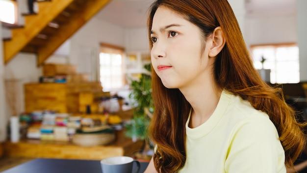Porträt der freiberuflichen freizeitkleidung der asiatischen frauen unter verwendung des laptops, der im wohnzimmer zu hause arbeitet. arbeiten von zu hause aus, fernarbeit, selbstisolierung, soziale distanzierung, quarantäne zur vorbeugung von koronaviren.