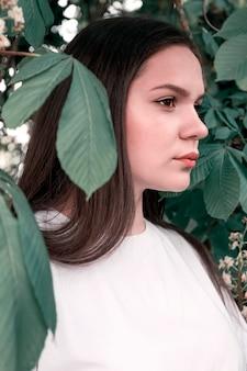 Porträt der freizeitbekleidung des jungen attraktiven mädchens auf hintergrund des kastanienbaums verlässt. konzept der jugend, lebensstil, natürliche schönheit.