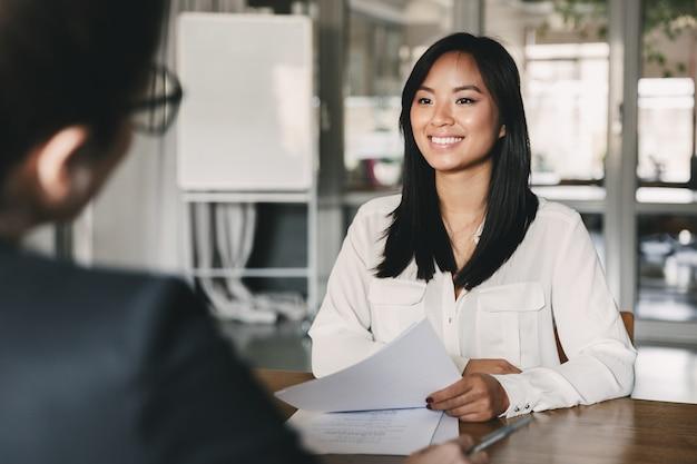 Porträt der freudigen asiatischen frau, die lächelt und lebenslauf hält, während sie während geschäftsbesprechung oder vorstellungsgespräch vor geschäftsfrau sitzt - geschäfts-, karriere- und vermittlungskonzept