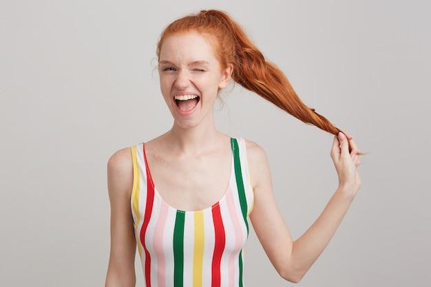 Porträt der freudigen attraktiven jungen frau mit roten haaren und sommersprossen