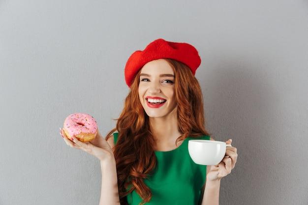 Porträt der freudigen eleganten dame mit ingwerhaar in der roten baskenmütze beim frühstück mit tasse kaffee und köstlichem donut, lokalisiert über graue wand