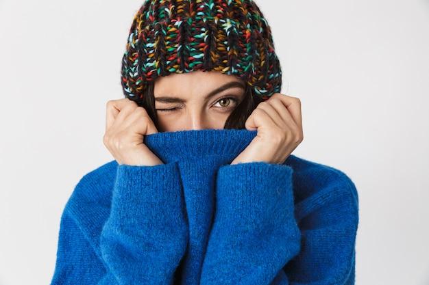 Porträt der freudigen frau, die wintermütze trägt, die im stehen lächelt, lokalisiert auf weiß