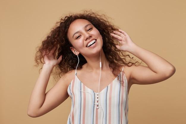 Porträt der freudigen jungen lockigen brünetten frau mit der lässigen frisur, die glücklich lächelt, während sie ihr lieblingslied hört, das auf beige mit erhobenen händen aufwirft